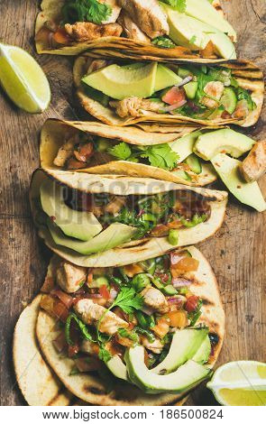 Tacos with grilled chicken, avocado, fresh salsa and limes over rustic wooden background, top view. Healthy low carb and low fat lunch or food for company. Dieting and weight loss concept