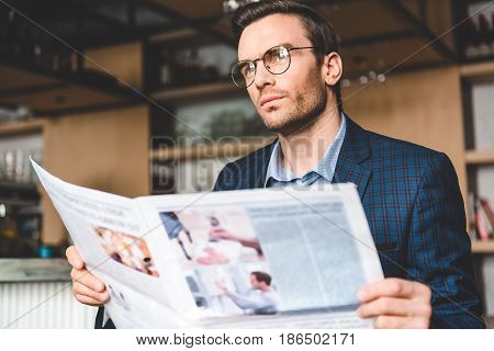 Low angle stubbled male demonstrating quietness while reading newspaper in comfortable confectionary shop