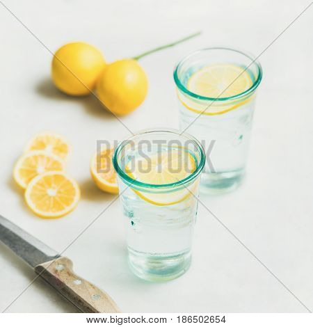 Morning detox lemon water in glasses and fresh lemons over marble background, selective focus, square crop. Clean eating, weight loss, healthy, detox, dieting concept