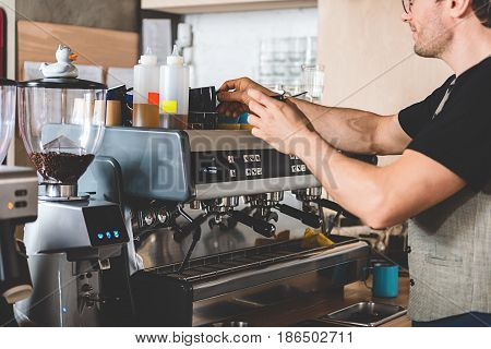 Cheerful bristled male preparing cup of delicious coffee with special machine in confectionary shop