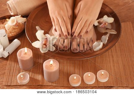 Female feet and hands with brown manicure in spa wooden bowl on bamboo mat