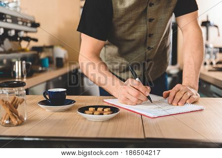 Barista writing new recipe of aroma delicious coffee in notebook. He standing at counter in confectionary shop. Close up of his arms