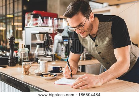 Cheerful bristled barista making notes for preparing delicious beverage in comfortable confectionary shop