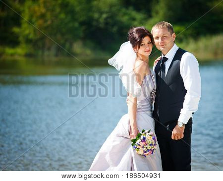Groom Hugs Bride Delicately Standing In The Front Of A Lake