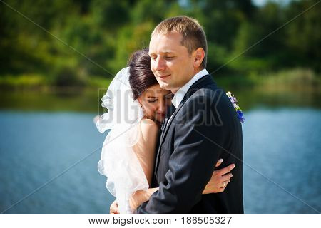 Bride Leans To A Groom Tightly Standing In The Front Of A Lake