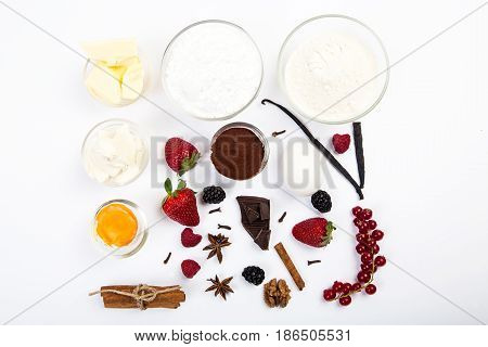 dessert ingredients and equipments on white wooden table. Berries, chocolate, eggs and other. Top view