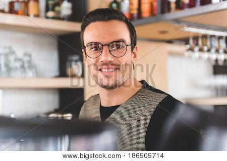 Portrait of stubbled man expressing happiness while working in confectionary shop