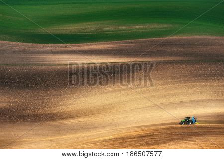 Farming tractor plowing and spraying on field.Small blue tractor working on a colorful spring field. Agriculture tractor  cultivating field and creating abstract background texture.Czech Republic. Spring in Europe