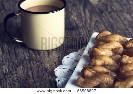 Metal mug full of coffee and a plate of koeksisters in an artistic conversion