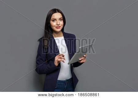 Business woman with digital device. Beautiful businesswoman at gray studio background with tablet