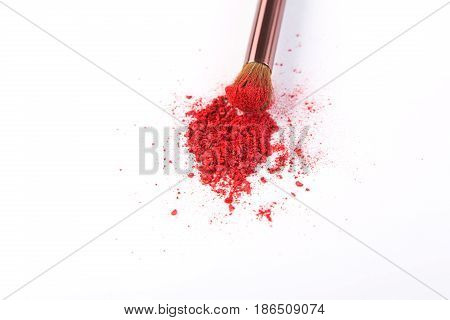 Makeup brush with red blush sprinkled on white. Make up and female cosmetics background