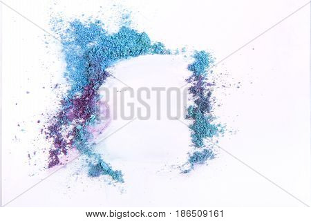 Makeup eyeshadow abstract frame background of blue and violet tones sprinkled on white. Make up and female cosmetics background