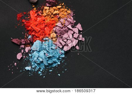 Beauty, makeup cosmetics. Eyeshadow splash palette, colorful crushed eye shadow powder, flat lay, top view, black background