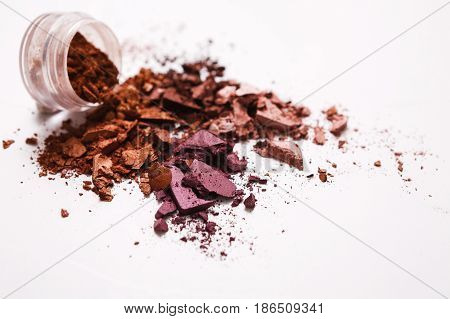 Makeup cosmetics. Eyeshadow crushed palette from jar, colorful eye shadow powder on white background