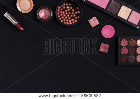 Makeup cosmetics and other essentials frame on black background. Top view, flat lay with copy space. Beauty tools palettes collection, lipstick, eyeshadow, blush, foundation and more