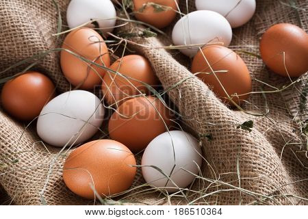 Poultry farm background. Fresh brown and white eggs on burlap with hay. Top view on sacking. Rural still life, natural healthy food concept.
