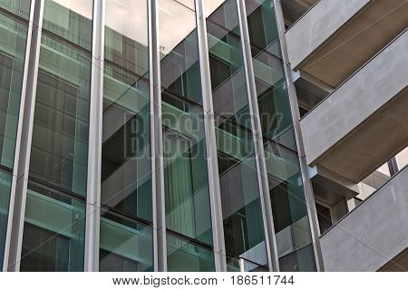 Disappearing glass lines of an office building. Vertical cladded facade with green tinted large windows