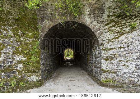 A old stone block tunnel leading to woods on the other side.
