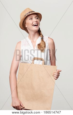 Happy laughing woman wearing summer straw hat holding craft shopping bag with empty copy space and looking away