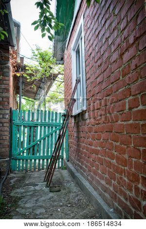 The backyard of a house in the Russian provinces : an old ladder leaning against the window of the house from a red brick