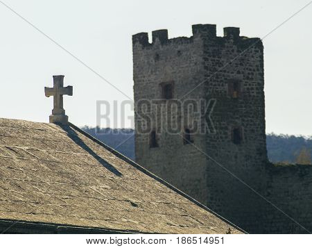An ancient cross on the roof and a fortress tower
