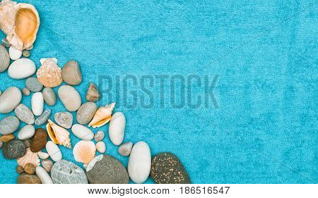Sea water pebbles on blue washcloth (towel) background with copy space. Simple sea resort flat layout background concept. Top view.