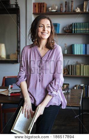 Portrait of a happy smiling mature woman leaning on the desk and holding a book indoors