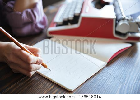 Close up portrait of a female hand holding pencil over open notebook on the table indoors