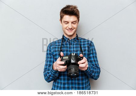 Pretty young man looking images at his camera isoalted over grey