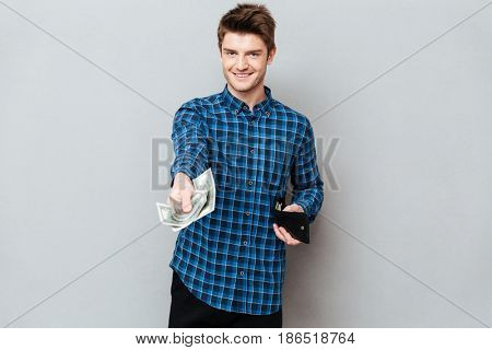 Young handsome man giving cash fron wallet to camera isolated