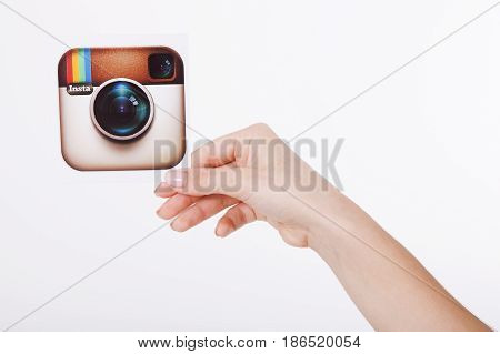 KIEV, UKRAINE - AUGUST 22, 2016: Woman hands holding Instagram logotype camera icon printed paper close up. Is an online mobile photo-sharing, video-sharing service.