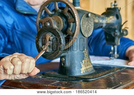 Elderly woman working on old sewing machine