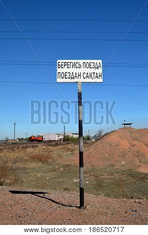 Road sign - Beware of train (RU and KZ).Area of former Soviet  anti-ballistic missile testing range.Kazakhstan.May 6, 2017.Sary Shagan.Kazakhstan