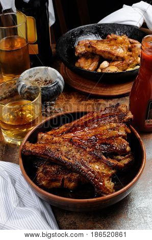 Fried spicy sharp pork ribs with beer and ketchup. Vertical shot.