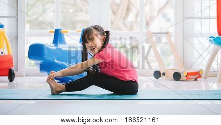 Unhappy asian children sitting on the mat unable to start yoga work out because of injury feeling pain