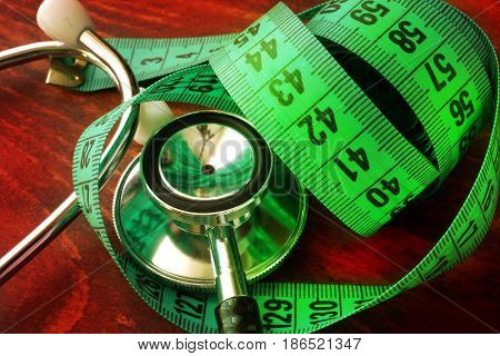 Medical weight loss concept. Measuring tape and stethoscope.