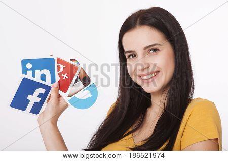 KIEV, UKRAINE - AUGUST 22, 2016:Woman hands holding collection of inscriptions, symbols of popular social media: Twitter, Google, Instagram, Fasebook, Linkedin, Snapchat printed on paper scattered randomly