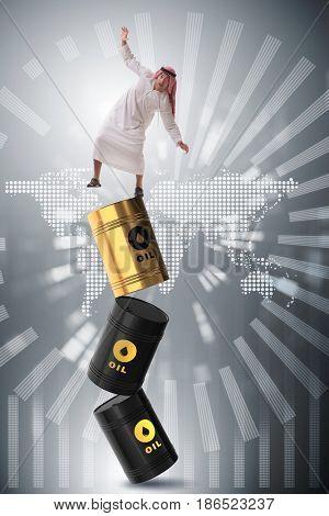 Arab businessman losing balance on oil barrels