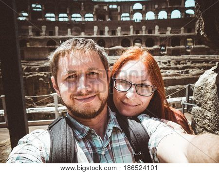 Selfie of the happy couple that stand against Colisee in Rome