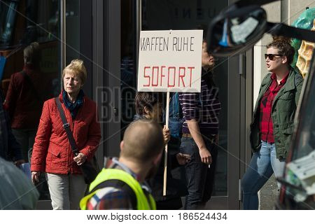 BERLIN - MAY 01 2016: Poster Ceasefire immediately. Members of trade unions workers and employees at the demonstration on the occasion of Labour day.