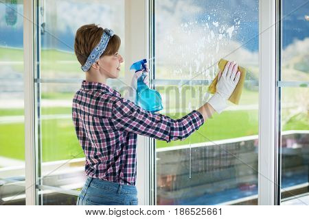 Woman is cleaning window. Woman with cleaning equipment