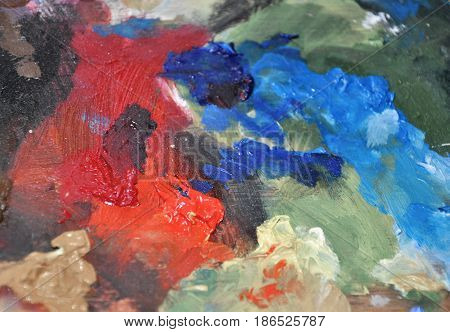 Detail of painter palette with bright red an blue oil paint colors