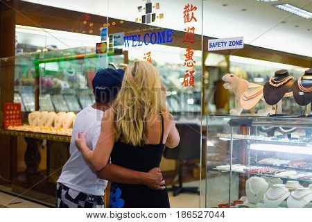 Pattaya Thailand May 19 2013: A young man and a girl are looking through the store window.