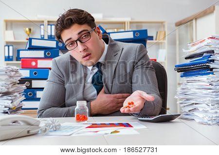 Sick businessman with medicines at work desk