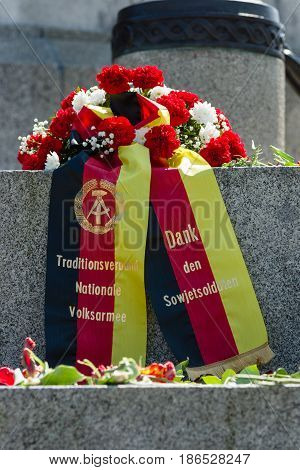 BERLIN - MAY 08 2016: Victory in Europe Day. A wreath in the colors of the German flag at the foot of the monument to Soldier - liberator in the Soviet War Memorial in Treptower Park. The inscription in German: Thanks to Soviet soldiers.