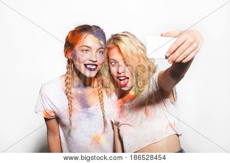 Cheerful young women standing on the white background covered with Holi colors taking a selfie.