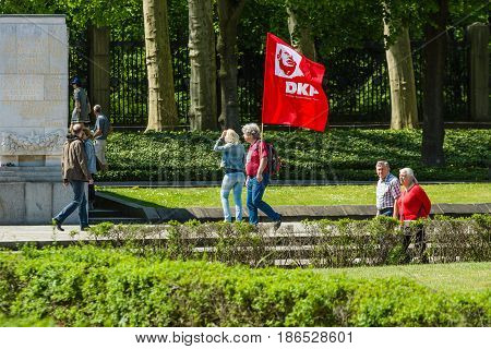 BERLIN - MAY 08 2016: Victory in Europe Day. Soviet War Memorial and military cemetery in Berlin's Treptower Park. A visitor with the flag of the German Communist Party.