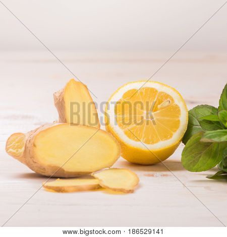 Ingredients for ginger lemonade: lemon, ginger, mint on a white wooden background. Detox water. Cleaning the body of toxins, vitamins