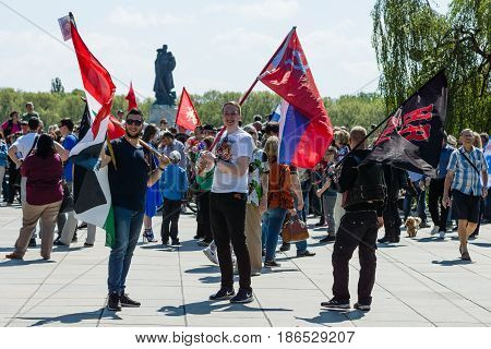 BERLIN - MAY 09 2016: Victory Day in Treptower Park. Guests with state flags of the Russian Federation the Syrian Arab Republic and the flag of the motorcycle club
