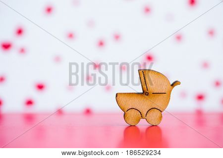 Wooden Icon Of Baby Buggy On Pink And White Background